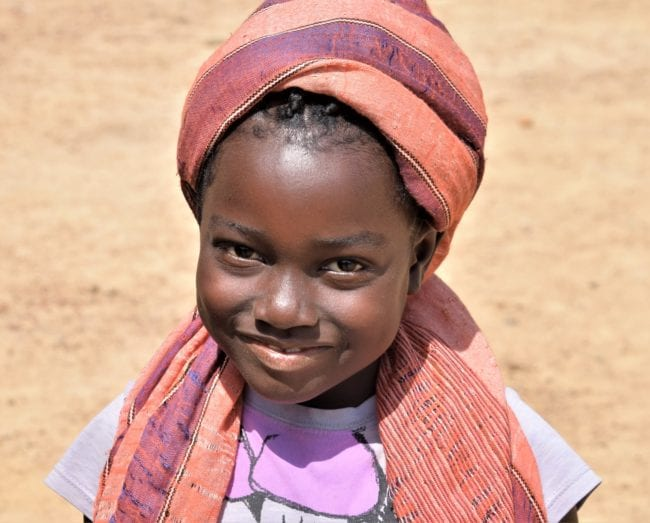 Portrait of a smiling young girl in an orange striped headscarf