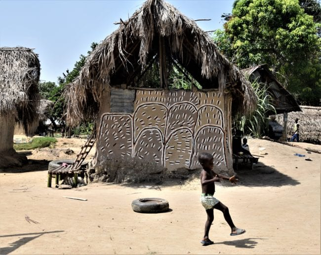 A boy plays outside a decorated village hut