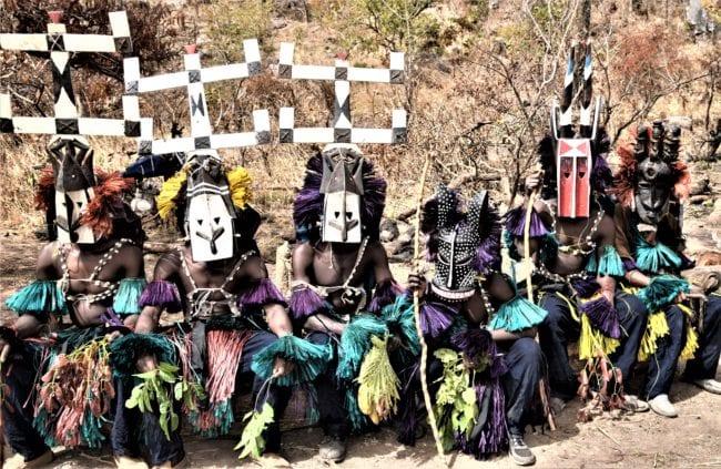 Dogon dancers sitting wearing assorted splendid masks, Mali