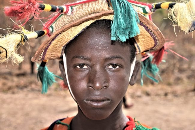 Portrait of a young Mandingo dancer in a tasselled hat