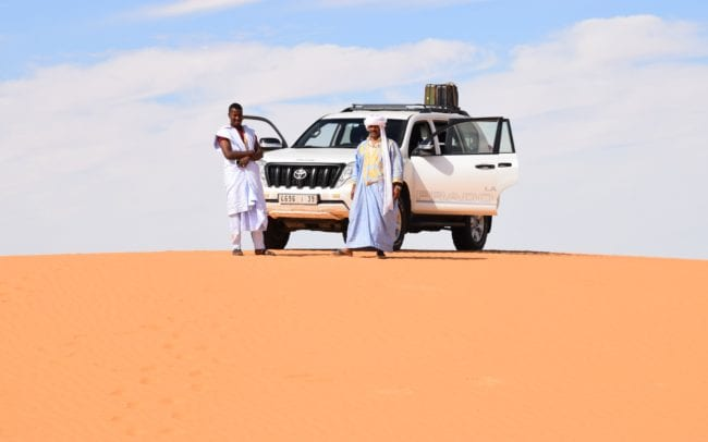Naji and Ahmed with the Landcruiser atop a sand dune