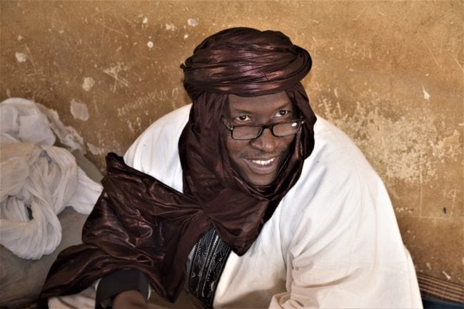 A portrait of a smiling man with glasses, wearing a trailing brown turban