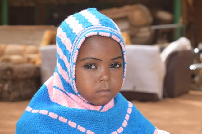 A portrait of a young girl in a knitted headscarf