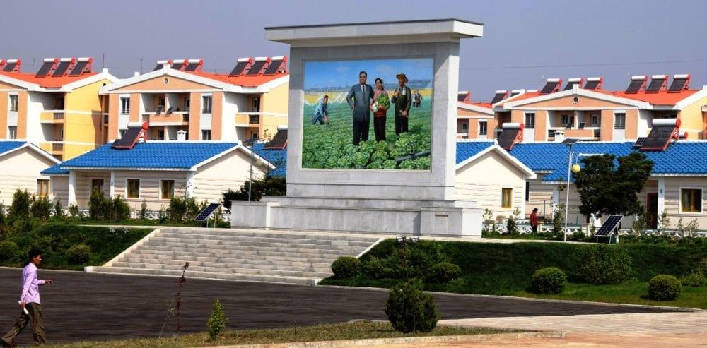 A propaganda poster in North Korea beside a colourful housing estate that serves a model farm