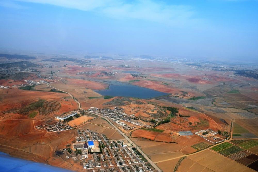 Flat red countryside outside Pyongyang North Korea