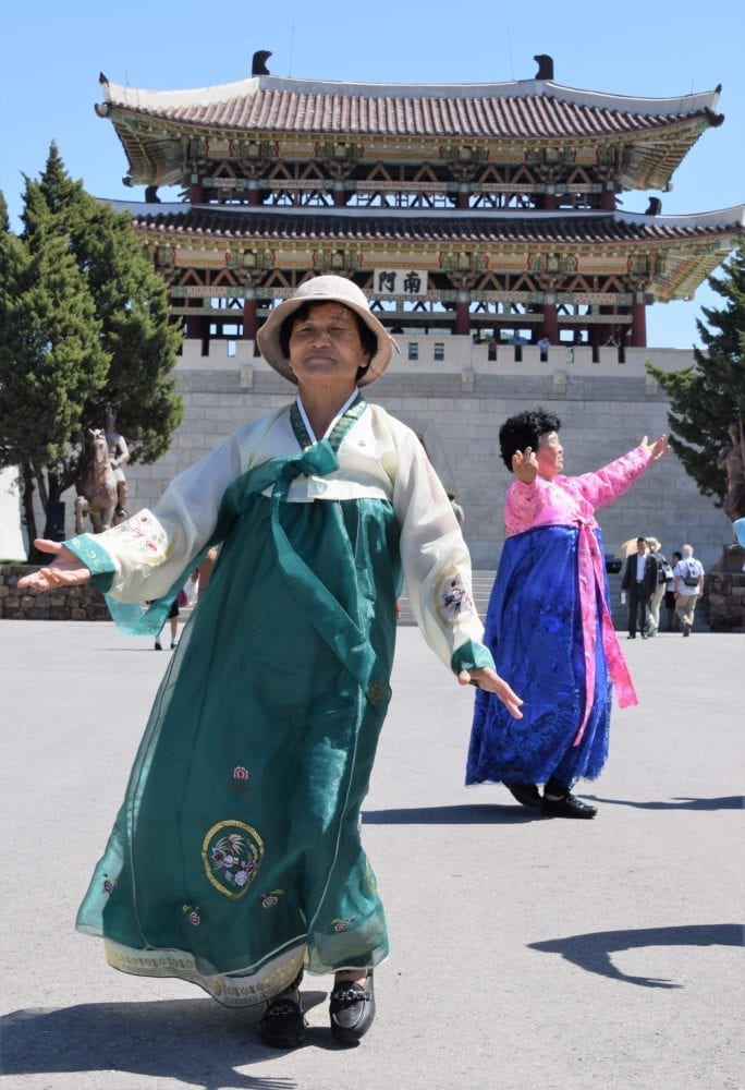 Ladies in national costume dance in front of a pagoda in the park on May Day in Pyongyang