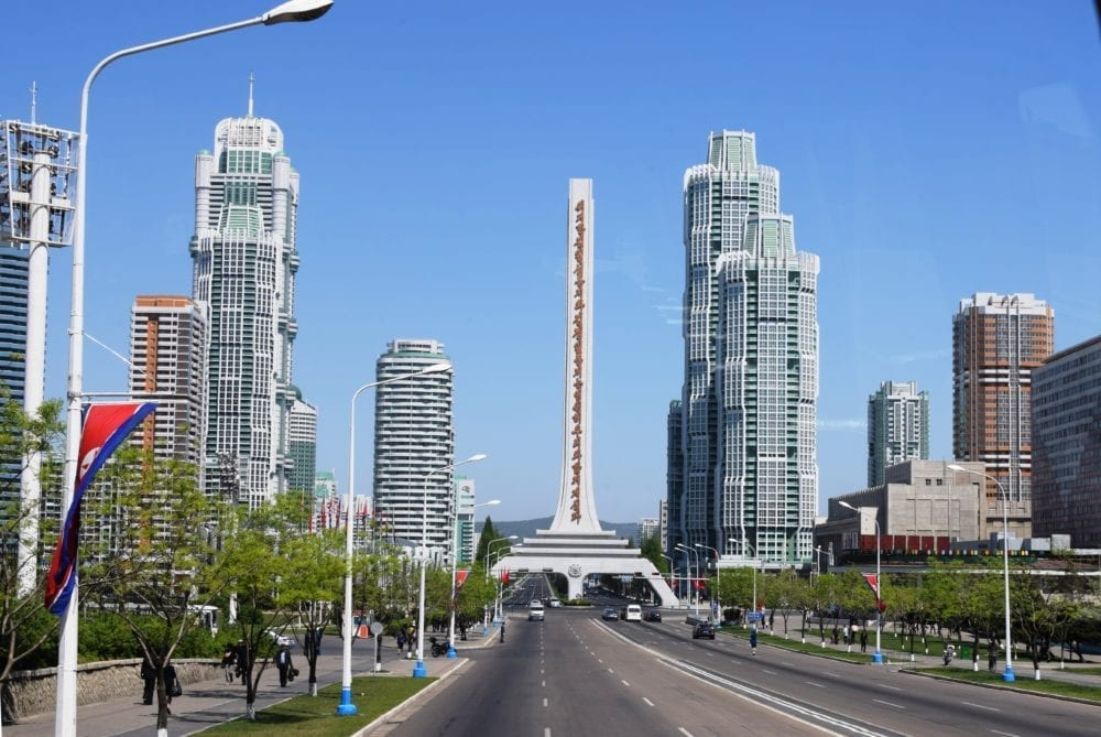 A highway, tall modern blocks of flats and a towering monument in Pyongyang