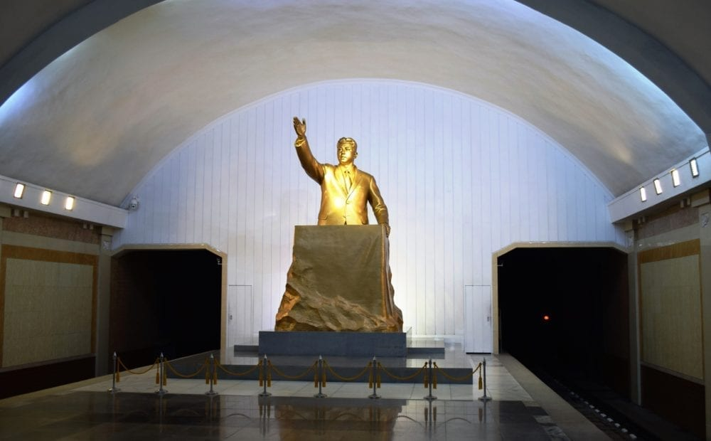 Gold statue of Kim Il Sung under an arch in the Pyongyang underground
