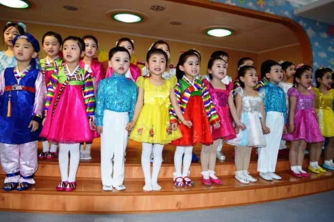 A large group of Kindergarten children in costume singing on stage in Pyongyang