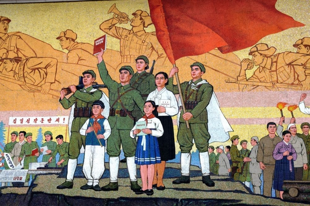 A patriotic underground station mosaic soldiers and school children carry a huge flag
