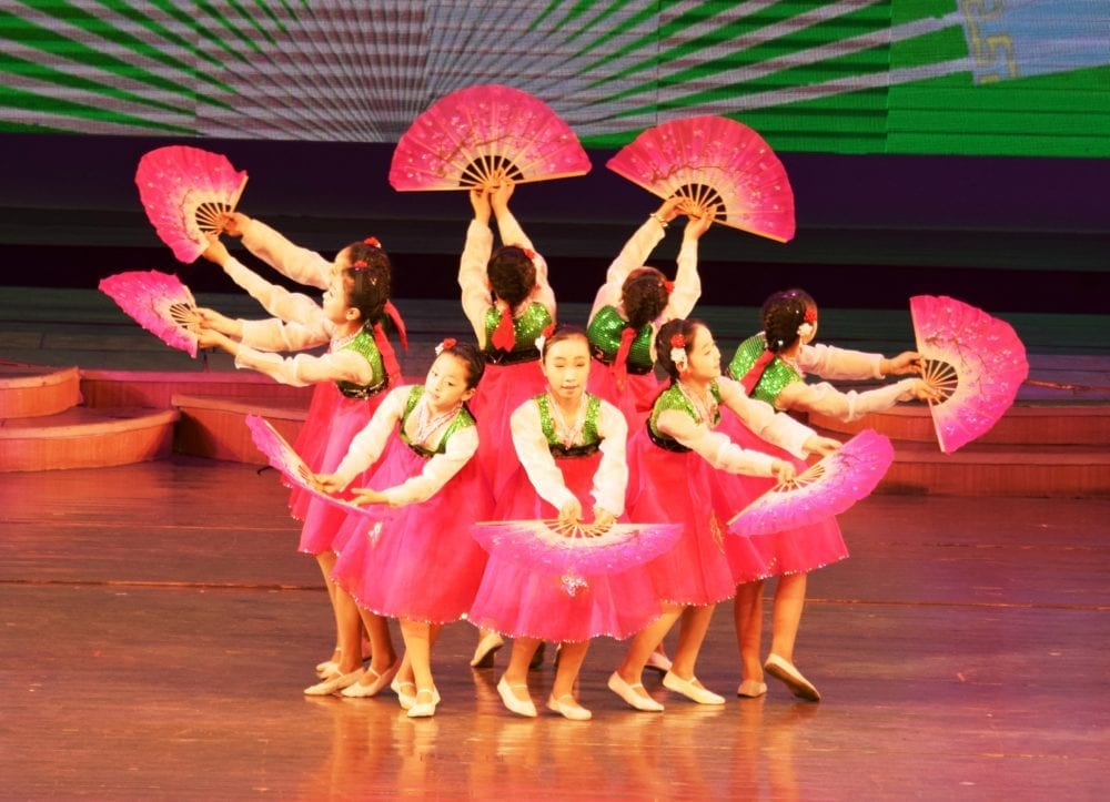 Secondary school girls dance with pink fans in Pyongyang