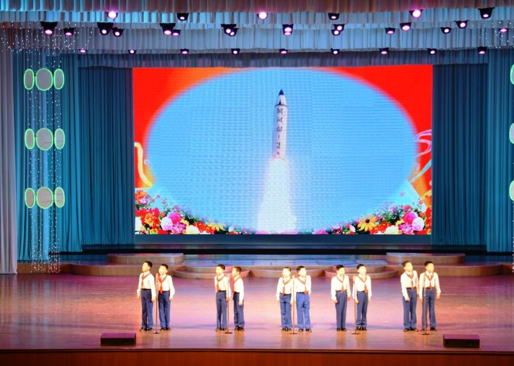 A rocket projected in the background during a secondary school stage performance in Pyongyang