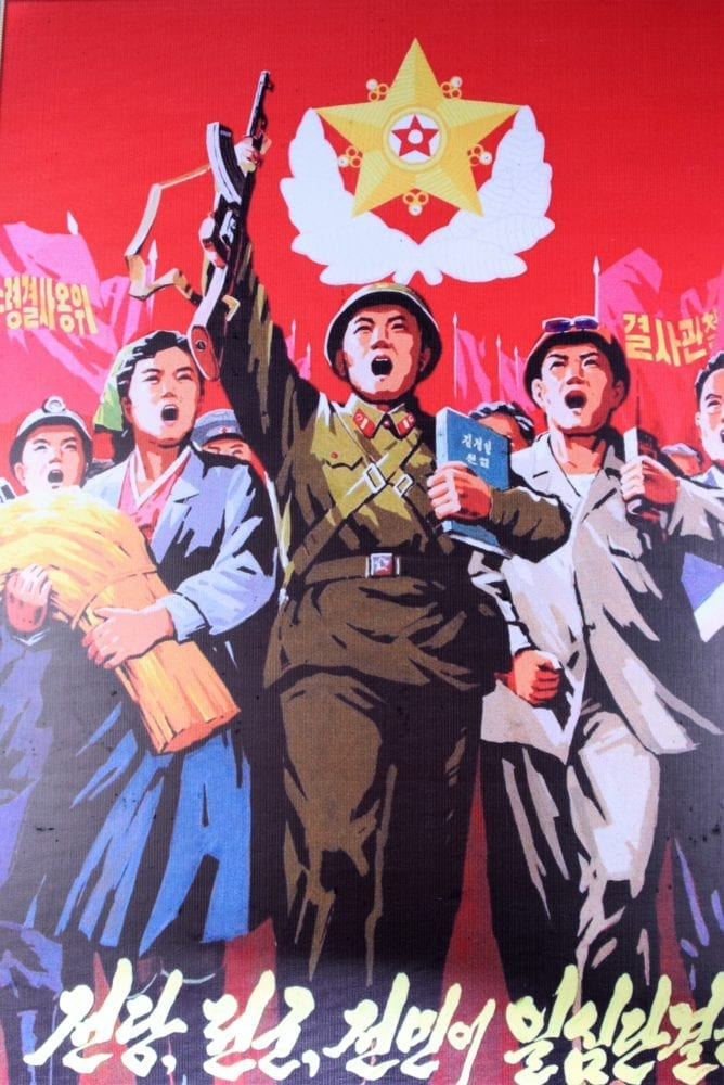 A patriotic poster in North Korea - marching people led by a soldier