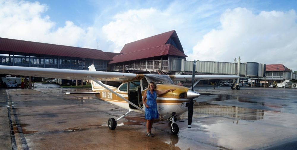 Sue in front of our small plane with the door removed