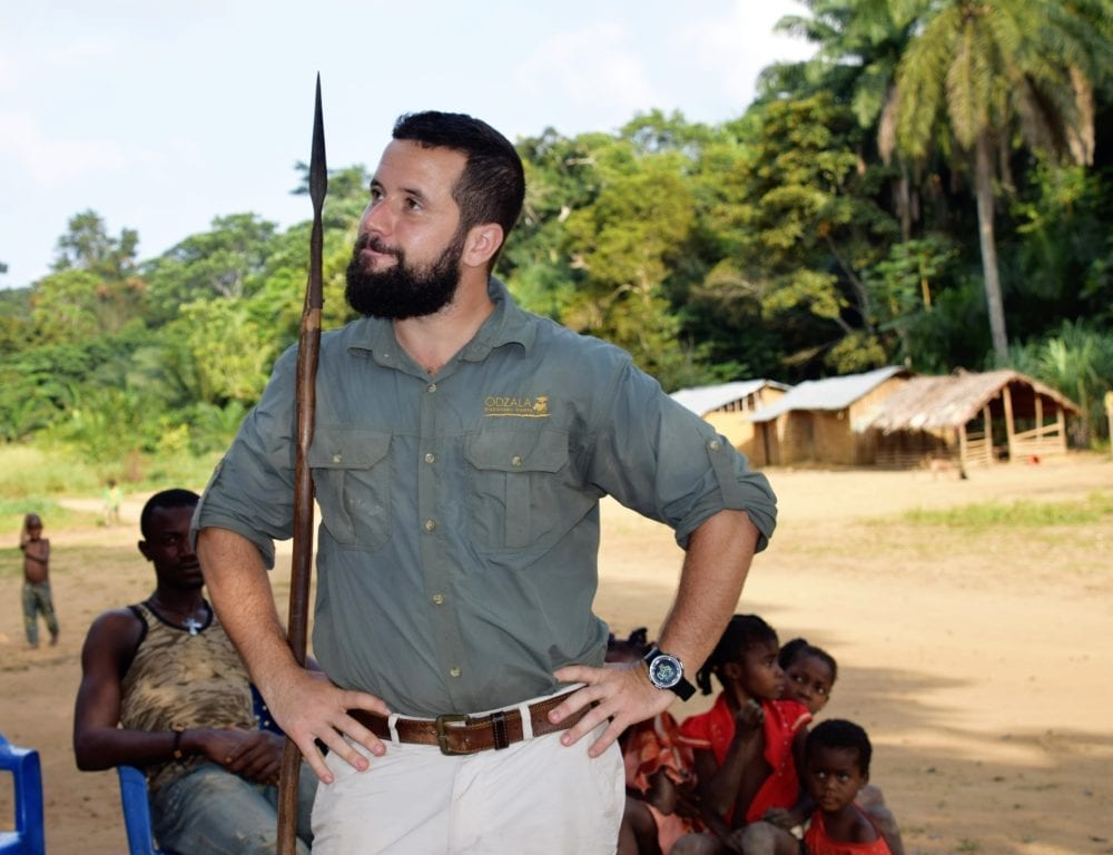 Guide Clem poses in the village at Odzala, holding a spear