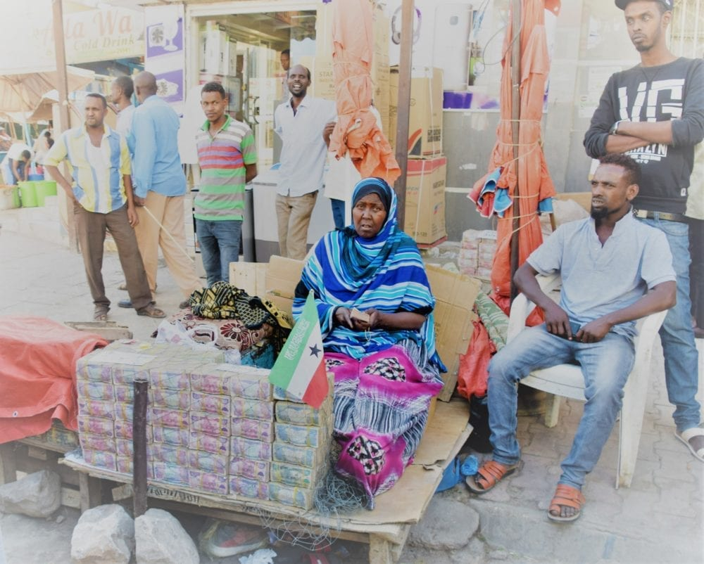 Moneychangers sitting with stacks of banknotes on the street in Hargeisa