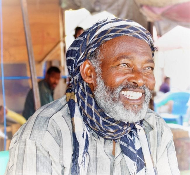 A headshot of smiling man with white beard in a blue check headscarf