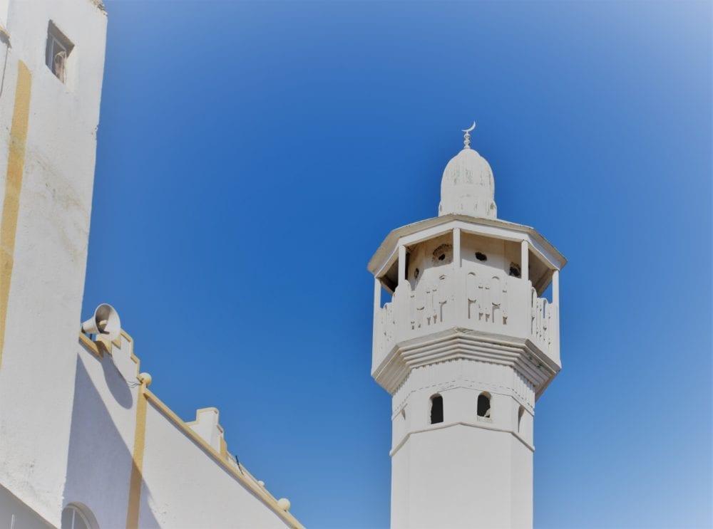 A white minaret framed by a blue sky
