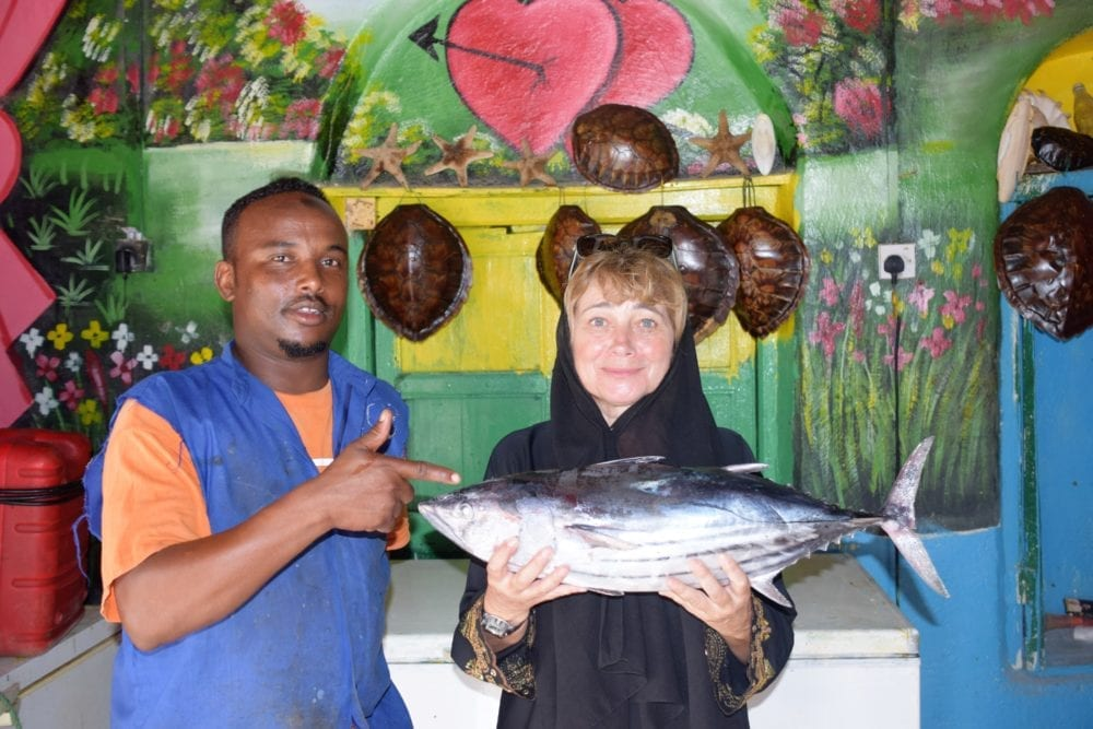 Sue in headscarf and abaya holding up a large fish in a fish shop in Berbera