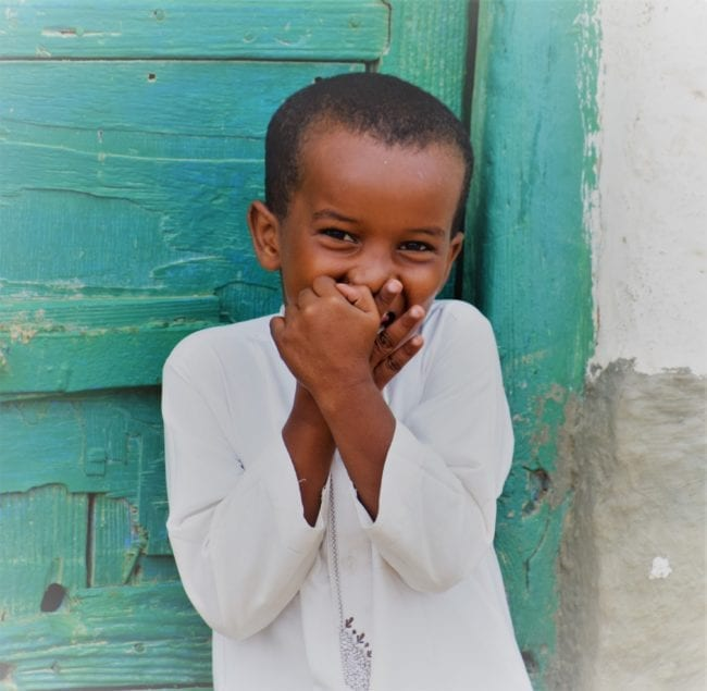 A headshot of a small boy giggling in front of a green door