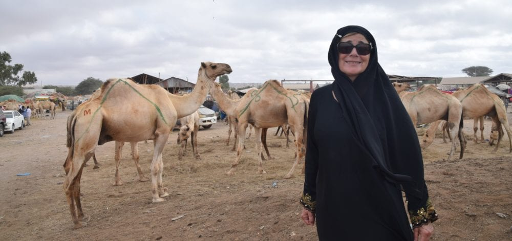 Sue in headscarf and abaya standing in front of camels at the market in Hargeisa