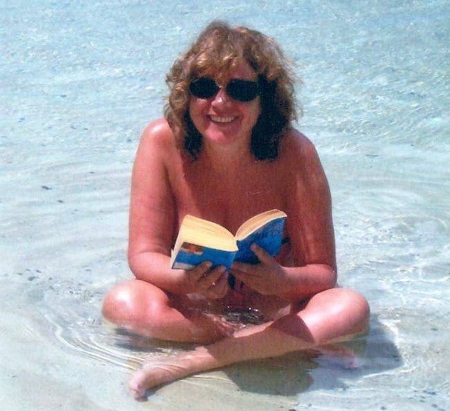 Sue sitting in the sea, reading, Tobago
