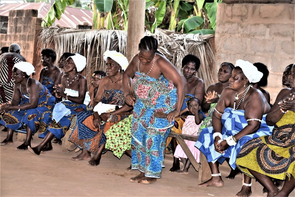 Togolese audience and woman dancing at the Voodoo ceremony