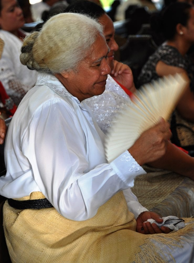 A lady with white hair and a fan in church in Nuku'alofa, Tonga