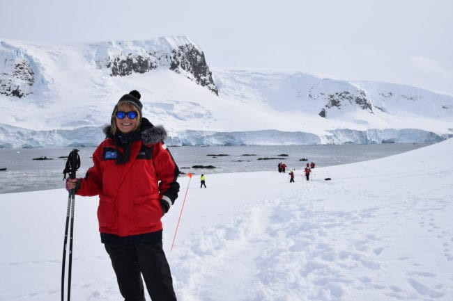 Sue in polar gear with walking poles wandering carefully on a track in the snow at Mikkelsen Harbour Antarctica
