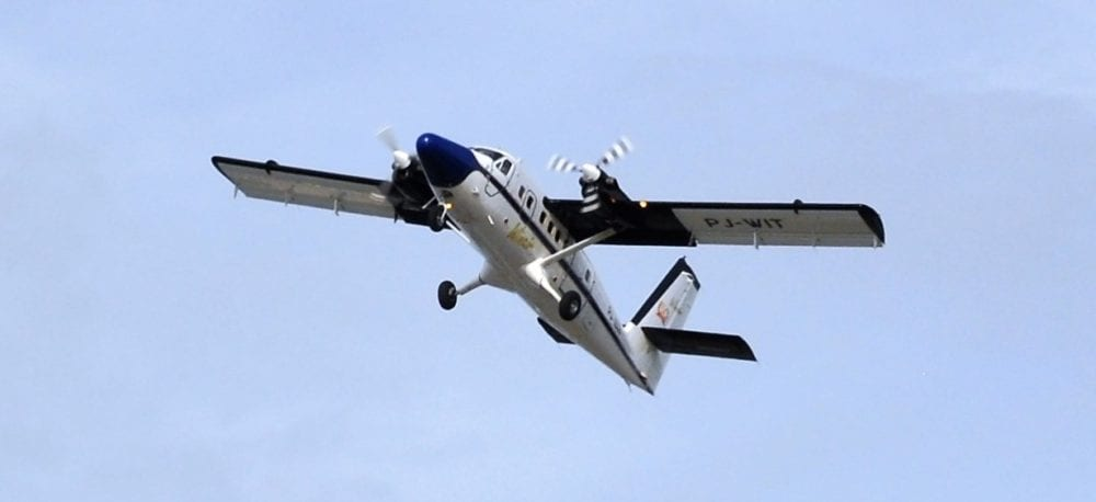 A blue and white prop plane takes off, Sint Maarten