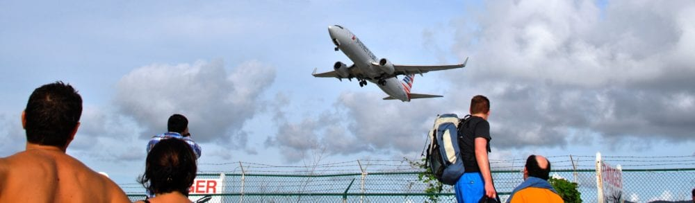 A jet plane takes off, over the airport fence at Maho Beach Sint Maarten