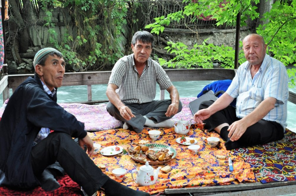 Surat and the drivers eat dinner by the river in Osh
