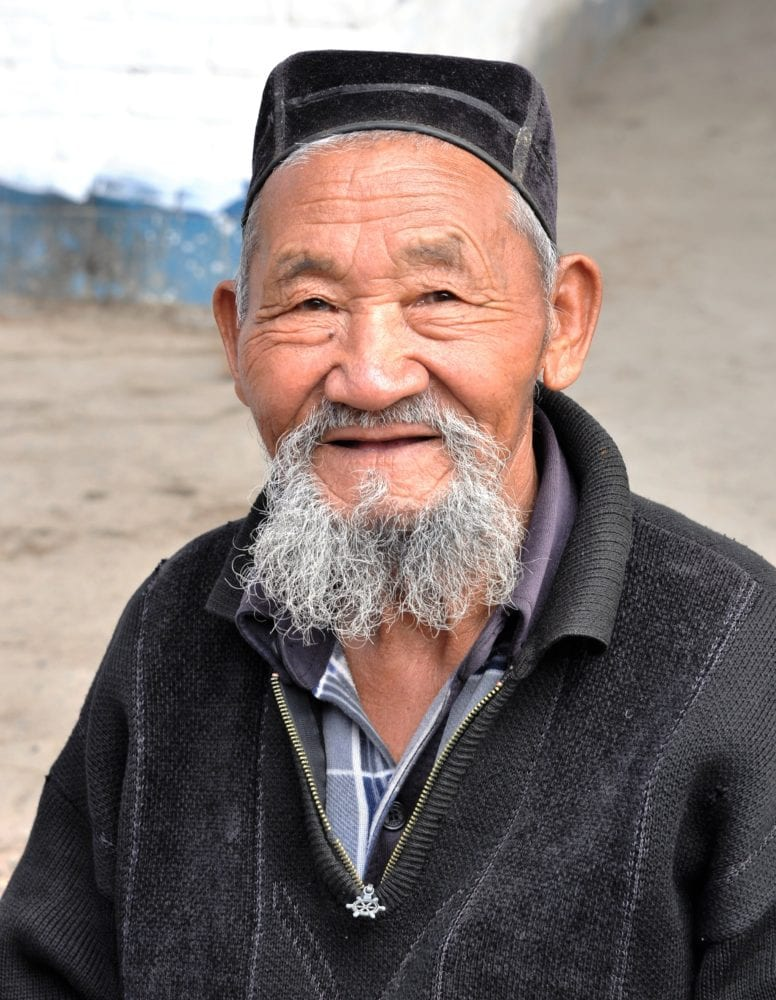 Portrait of a Kyrgyz man with grizzled beard and skull cap