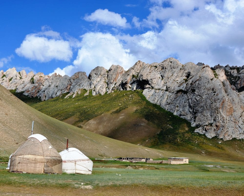 Two yurts framed by tooth shaped mountains at Tash Rabat, Kyrgyzstan