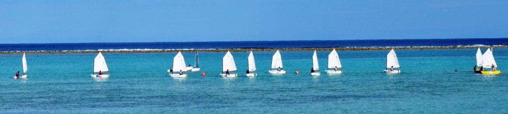 A flotilla of sailing dinghies in the lagoon at Rarotonga