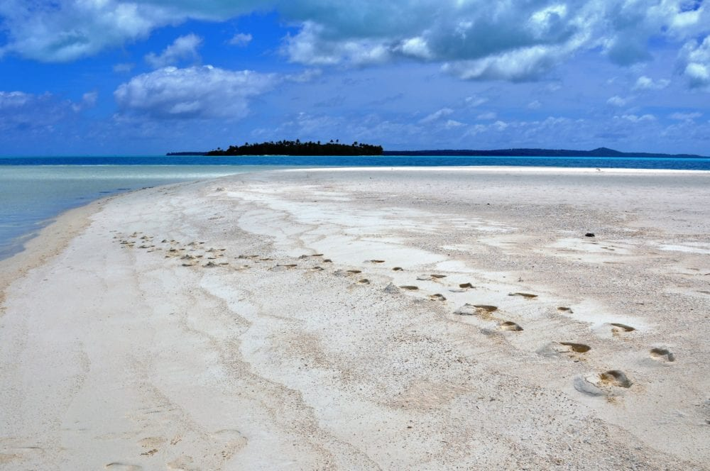 Foostpes in the sand on the end of a small island , more motus in the sea behind on Aitutaki Lagoon