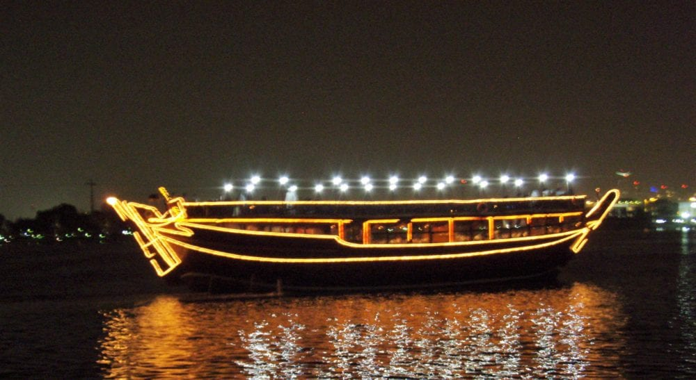 A dhow in the harbour illuminated at night