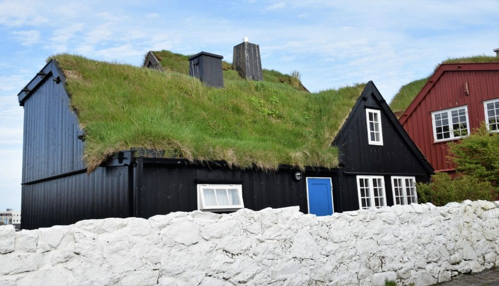 A typical timber house with black walls and green turf roof, Faroe Islands