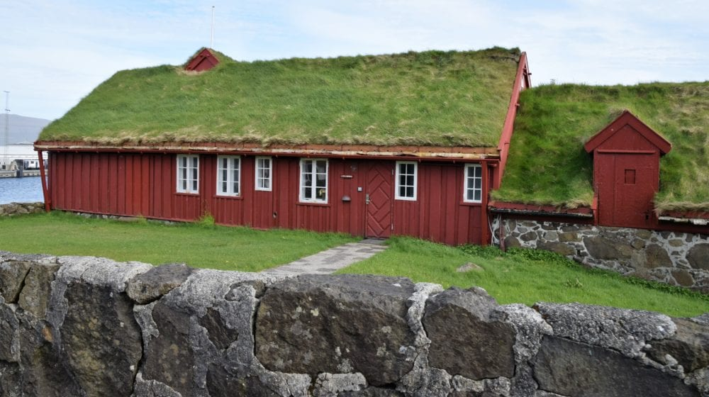 A typical timber house with red brown walls and green turf roof, Faroe Islands