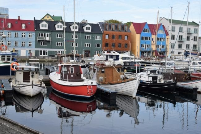 Bright houses and boats reflected in the water at Torshavn harbour