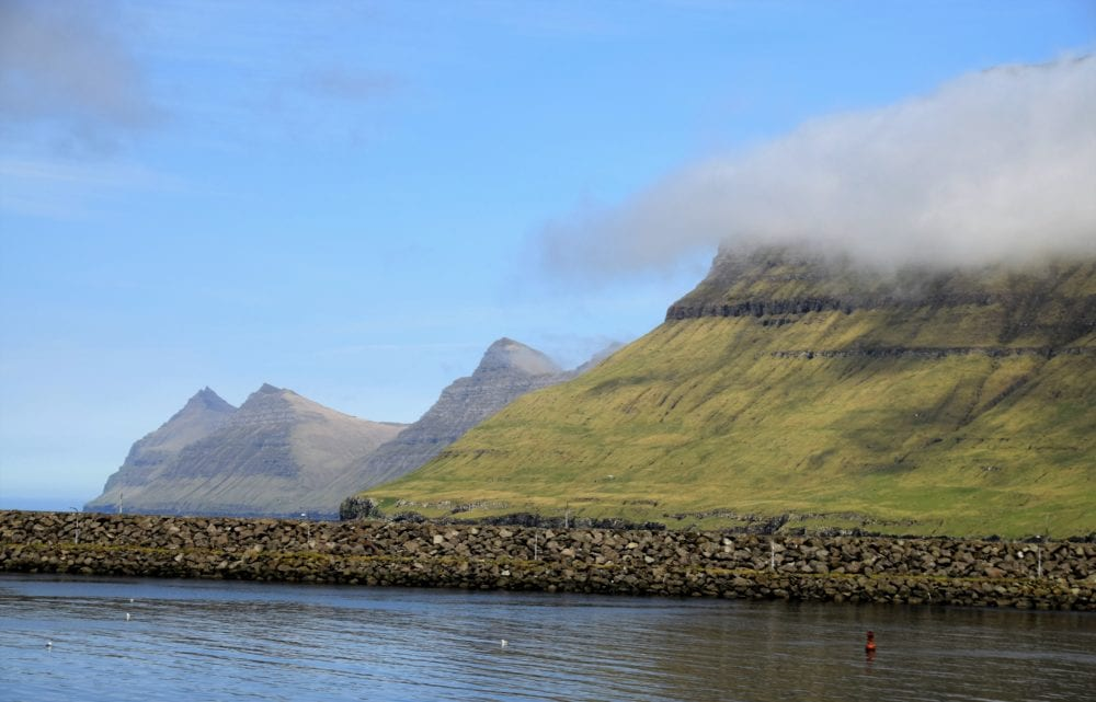 Clouds passing in front of a steep velvety sided fjord, mountain peaks in the background, Faroe Islands