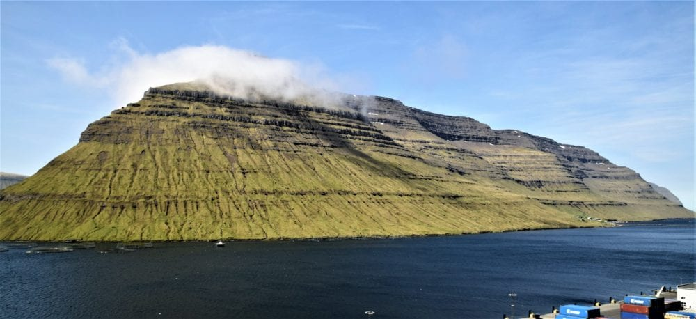 Steep sided peak, by the fjord, rising in to the clouds, Faroe Islands