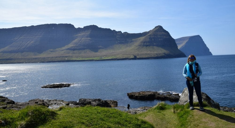 Sue on a fjord edge, in front of some jutting peaks, Faroe Islands