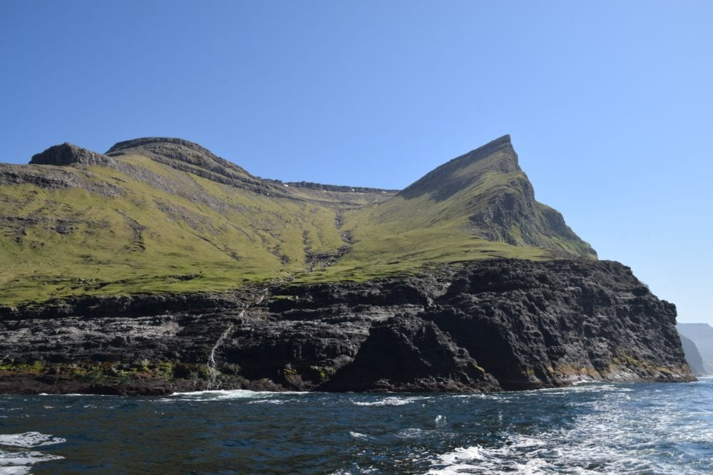 Velvety topped cliffs and a ribbon waterfall at Vestmanna Bird Cliffs