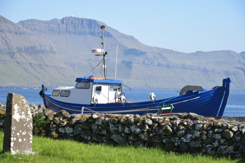 A blue fishing boat moored at Vestmanna