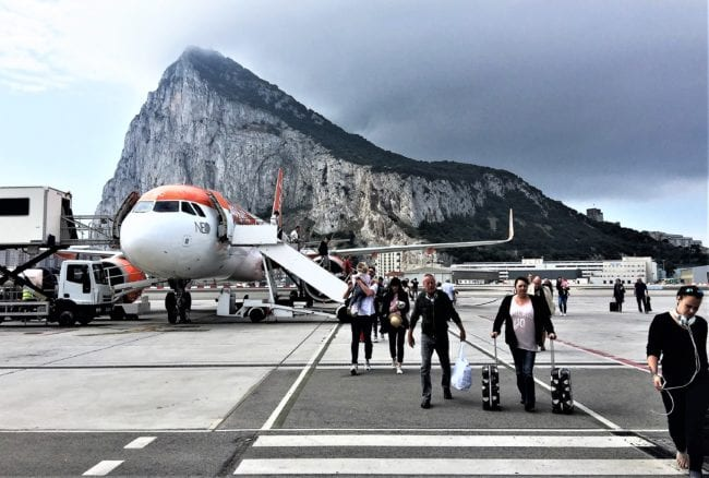 Passengers disembarking from the EasyJet flight at Gibraltar, The Rock is behind