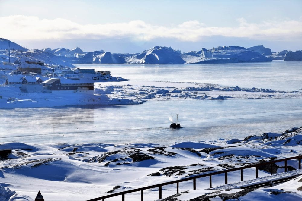A fishing boat chugs through a channel in the icy blue water out into the Icefjord