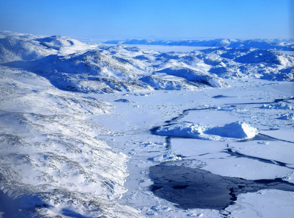 Icebergs in an icy bay backed by snow covered mountains seen from the air, Greenland