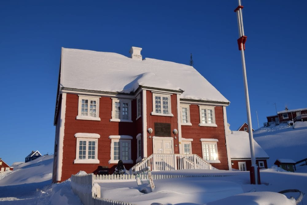 A cinnamon coloured timber house with snow on the roof, Ilulissat