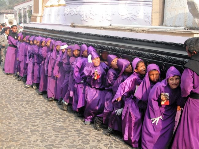Boys in purple hooded robes carry tableaux at the Semana Santa procession, Antigua